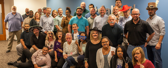 TrialCard employees with beards, moustaches and paper moustaches on sticks pose together after participating in the 6th annual Movember no shave November