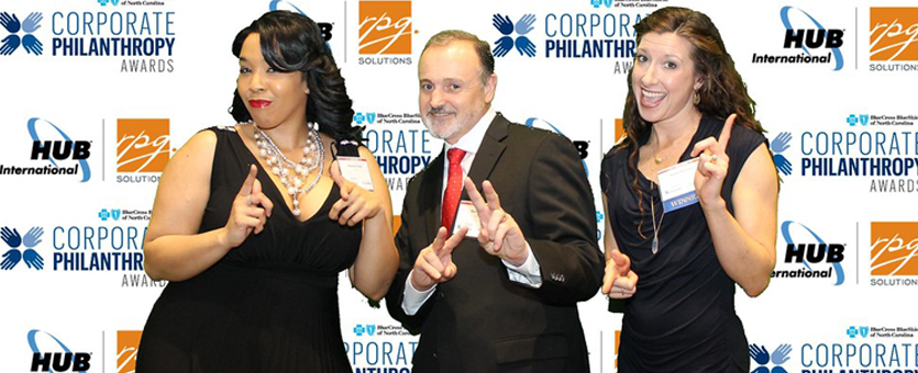 Three TrialCard employees pose after accepting the Triangle Business Journal Corporate Philanthropy Award