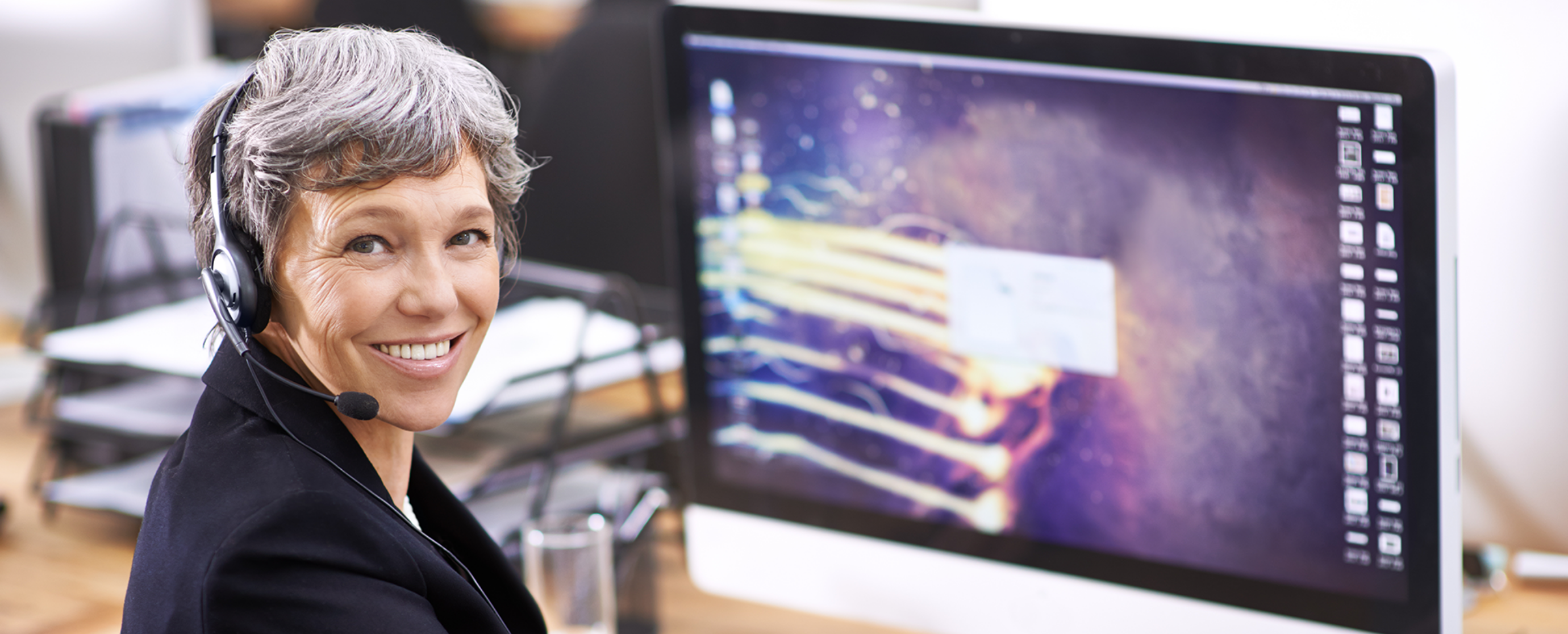 A woman wearing a headset in front of a large computer screen turns and smiles