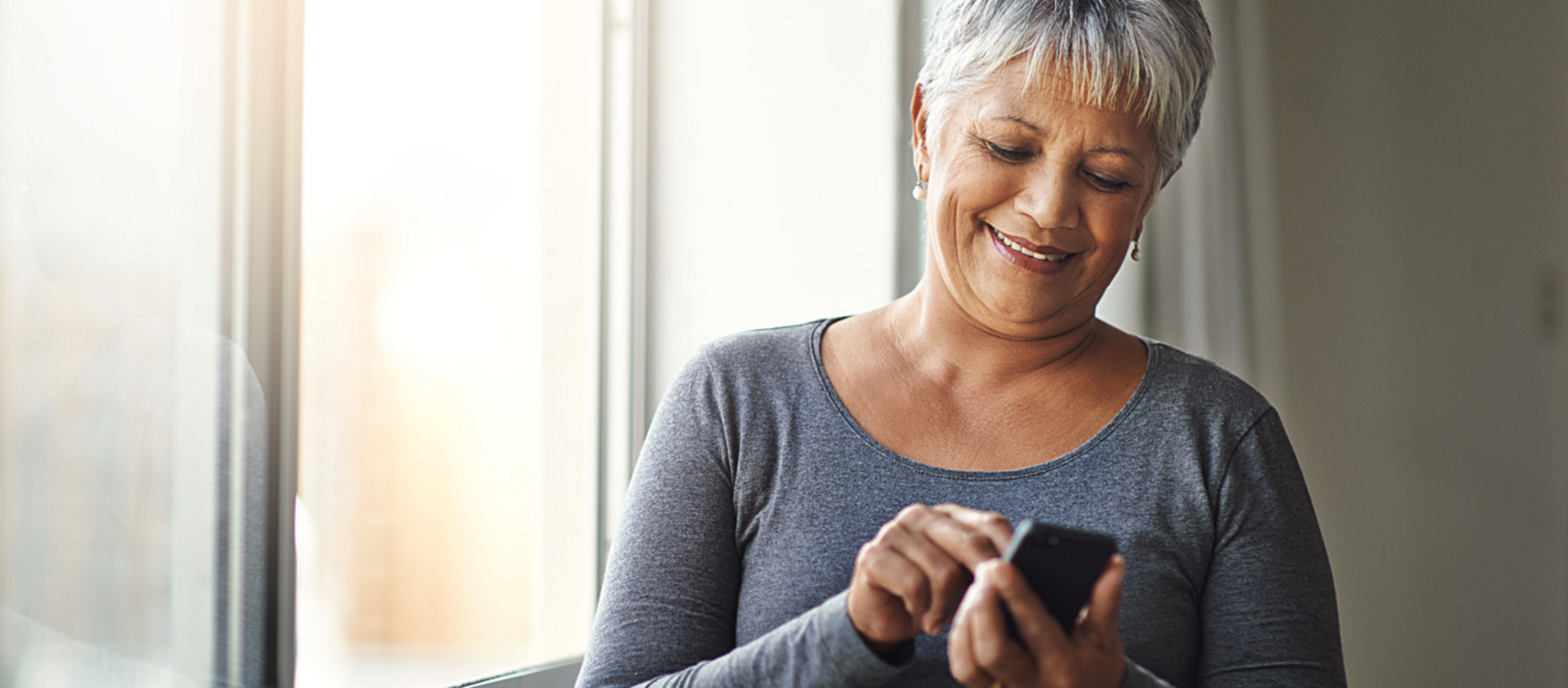 Older woman with short gray hair smiles while scrolling on her cell phone