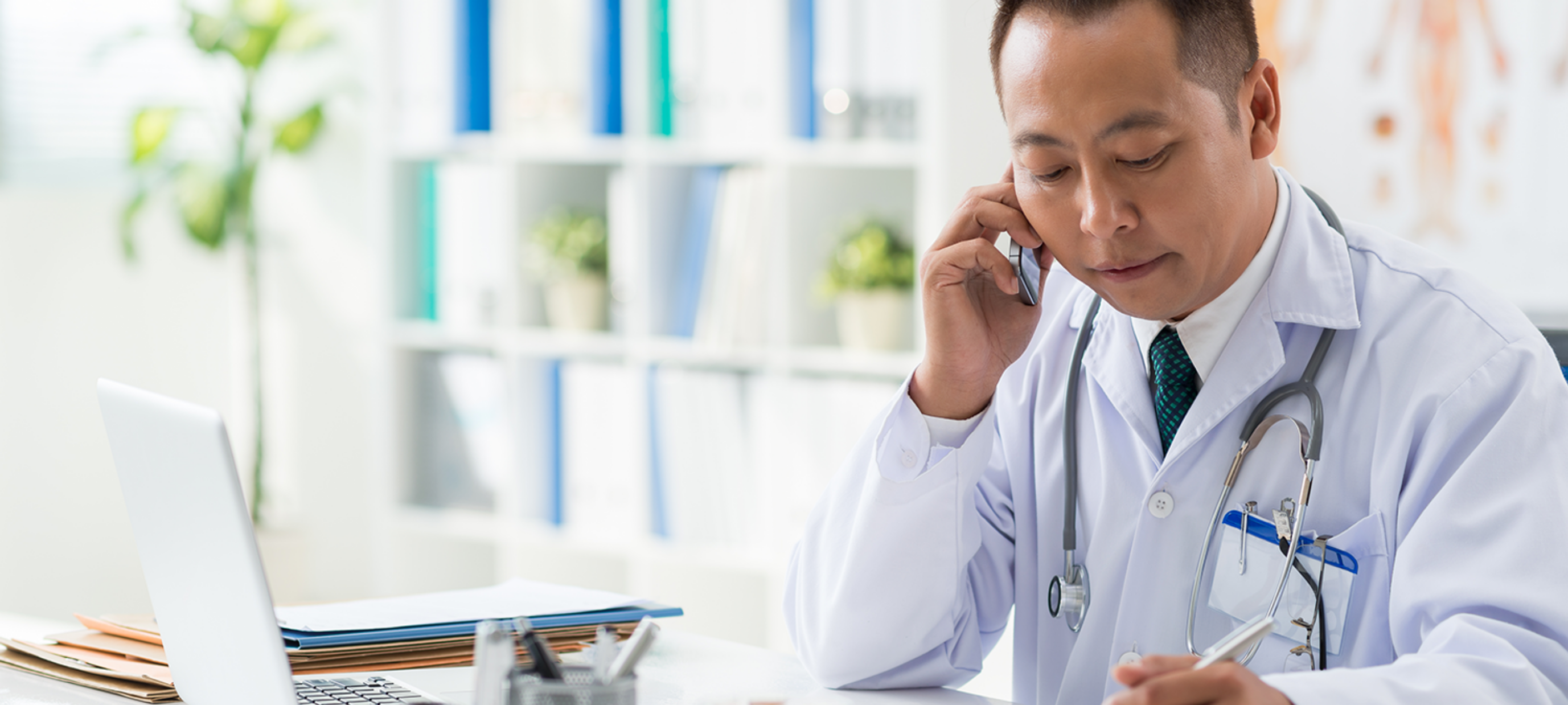 Photo of an Asian man wearing a white lab coat and a stethoscope, listening intently on the phone