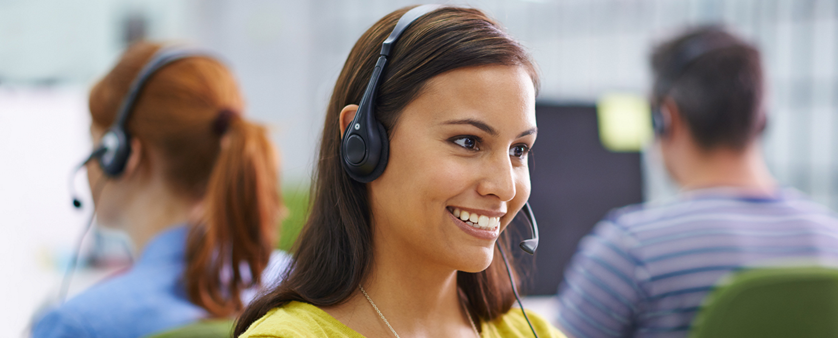 Smiling woman with headset at a call center.