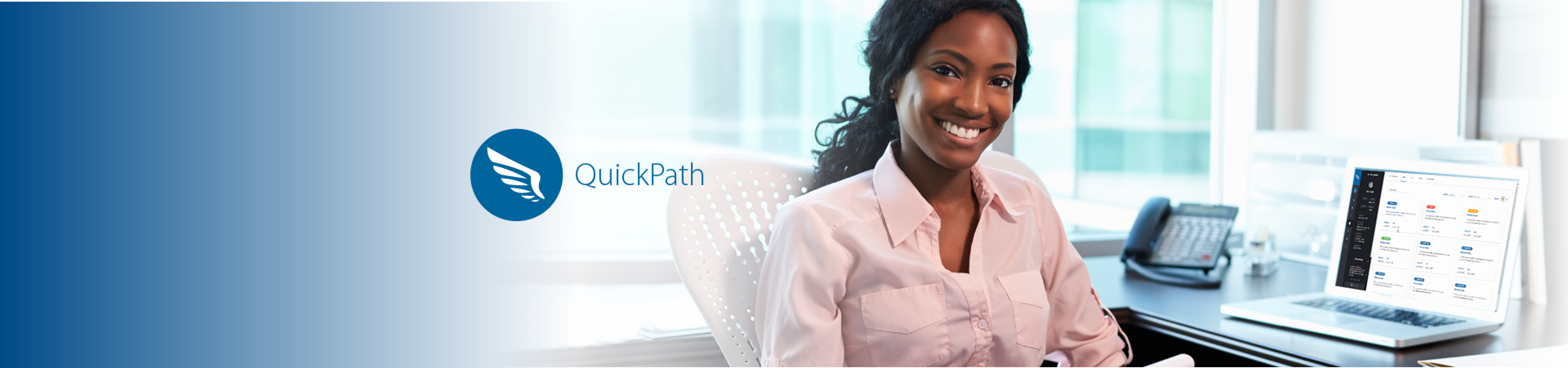 A smiling African-American woman sits at her desk; the QuickPath logo is to the left of the image